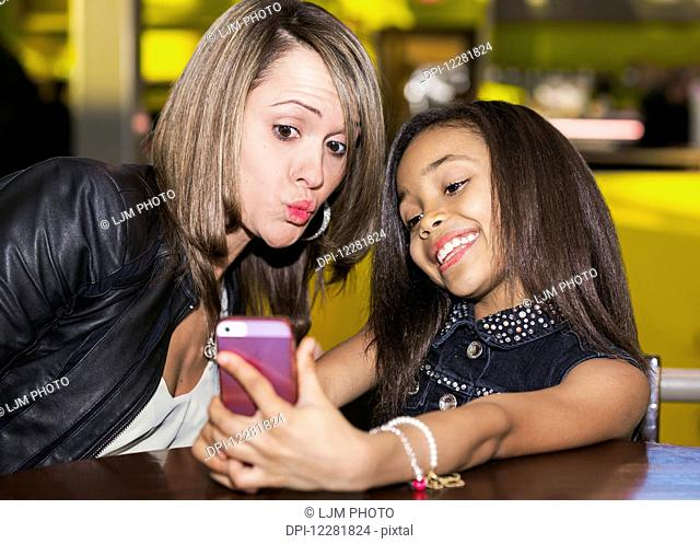 Young mother and her daughter in a cafe looking at a smart phone and taking a selfie while taking a break from shopping; St. Albert, Alberta, Canada