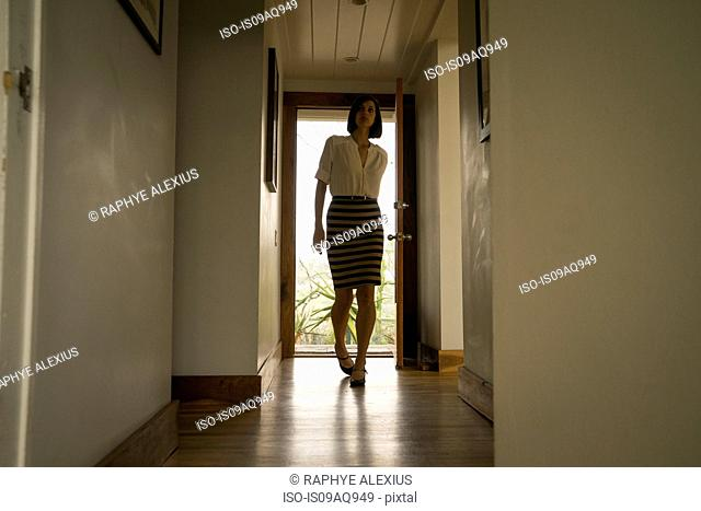 Mid adult woman arriving in house hallway