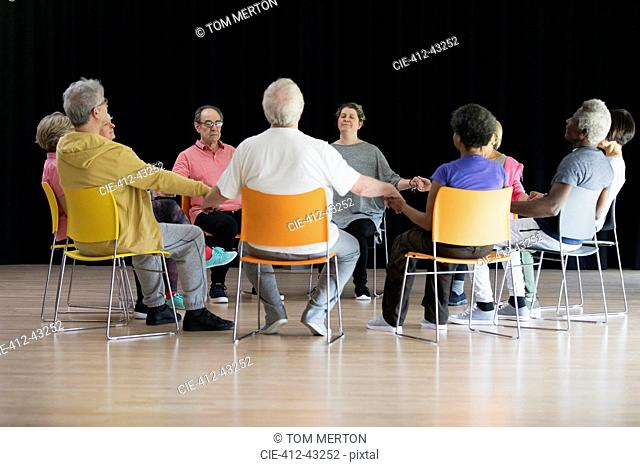 Active seniors meditating, holding hands in circle