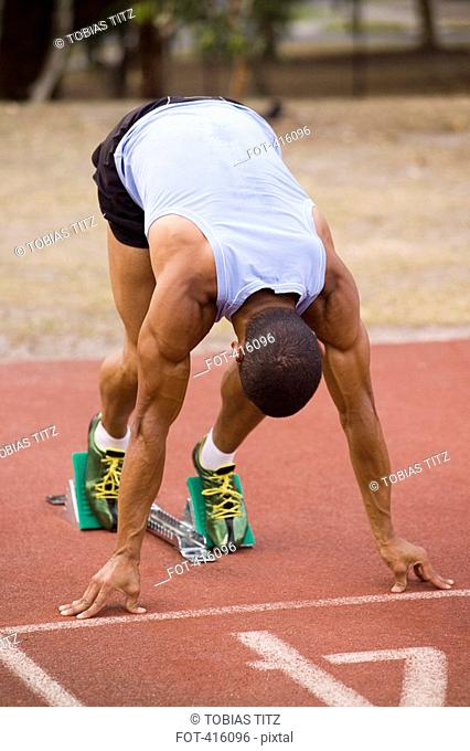 Male athlete in starting blocks on a running track