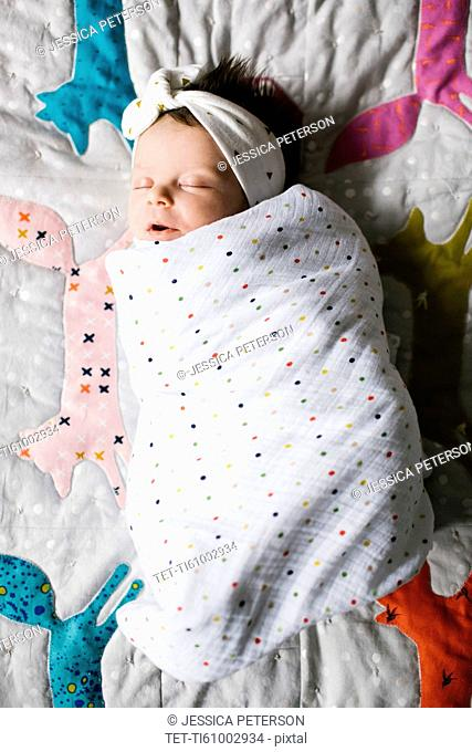 Baby girl (0-1 months) wrapped in blanket sleeping on bed