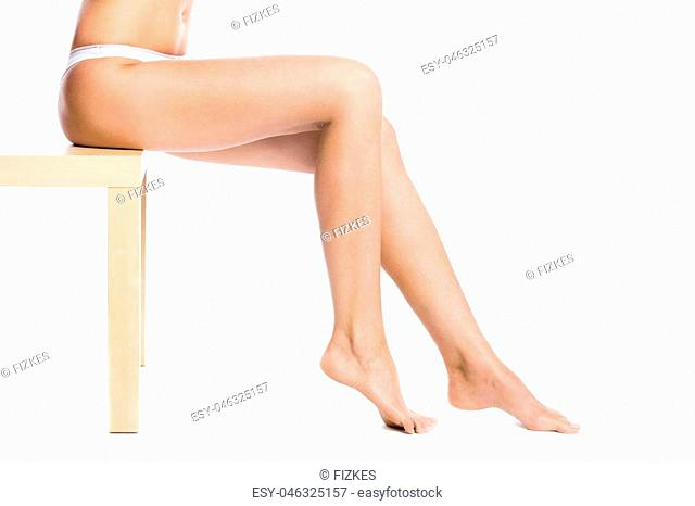 Close-up of long legs of beautiful attractive Caucasian young model sitting on table against white background. Pretty person with perfect legs posing