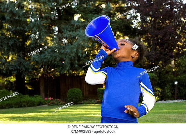 A little black girl dressed as a cheerleader for Halloween yelling through a megaphone