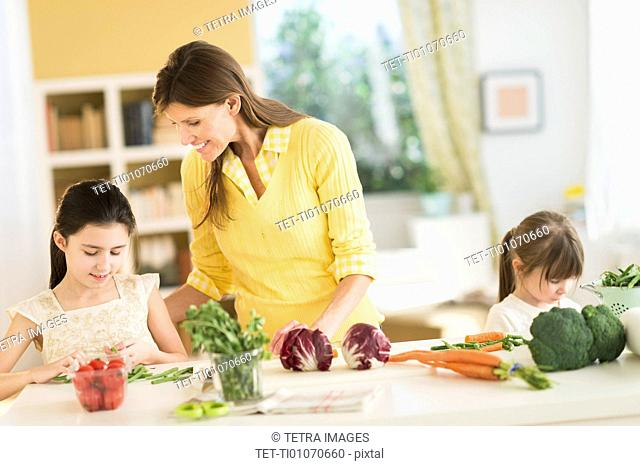 Mother and daughters (4-5,8-9) cooking in kitchen