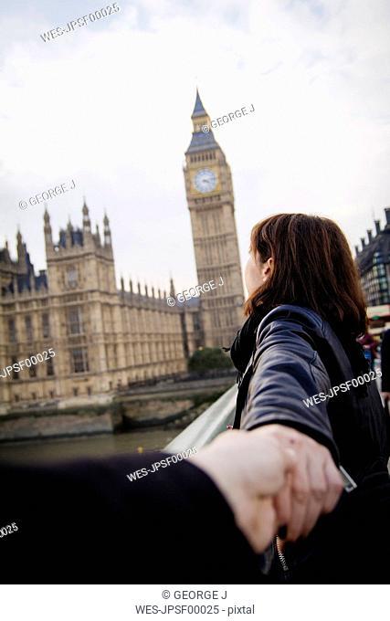 UK, London, woman pulling friend towards Big Ben