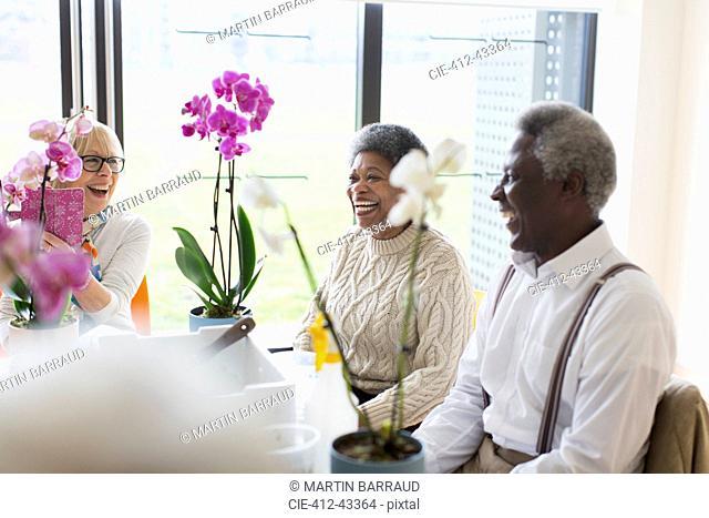 Happy active seniors enjoying flower arranging class
