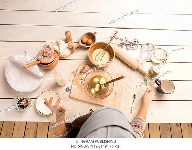 Woman baking Christmas cookies in her kitchen. Top view