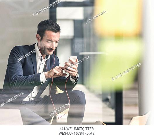 Businessman talking on the phone, using earphones