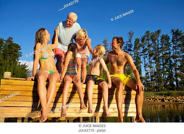 Portrait of multi generation family sat on jetty beside lake