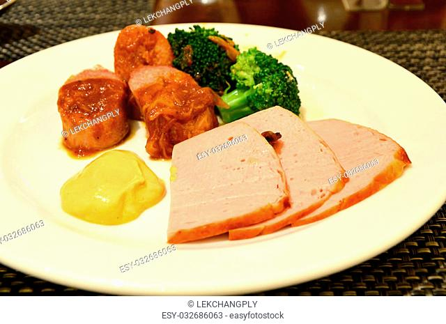 slice meet and sausage with broccoli on white plate
