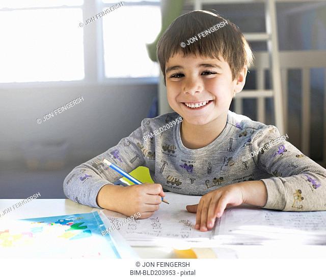Hispanic boy doing homework at desk