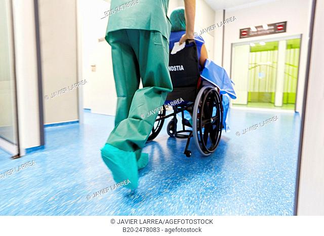 Doctor pushing wheelchair with patient in hospital corridor, transferring patient to the operating room, Ambulatory Surgery, Hospital Donostia, San Sebastian