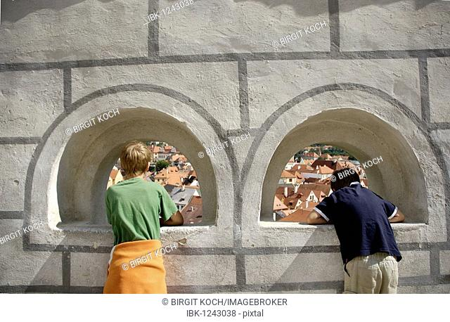 Two children looking through a window in the castle wall, Cesky Krumlov, UNESCO World Heritage Site, South Bohemia, Bohemia, Czech Republic, Europe