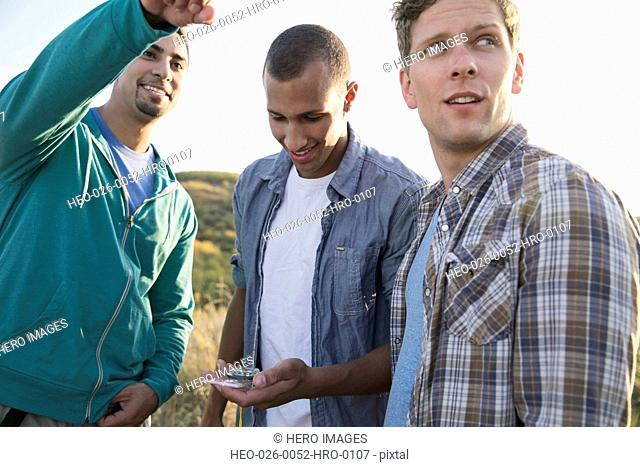Three men using compass to determine direction