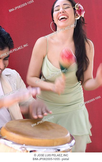 Woman dancing while man plays conga