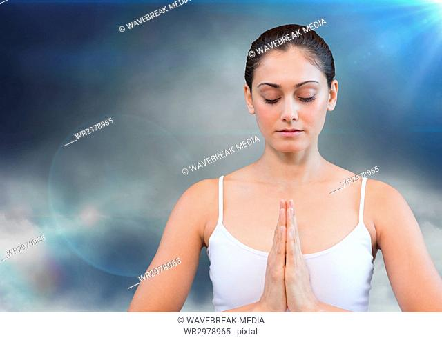 Woman meditating against cloud and flares