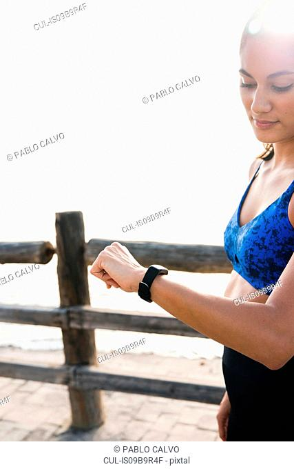 Young woman training on sea waterfront, looking at smartwatch