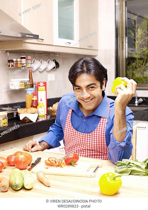 Young man holding capsicum in hand sitting in kitchen MR702V