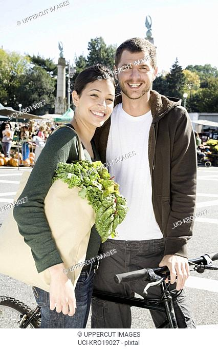 Multi-ethnic couple with bag of vegetables