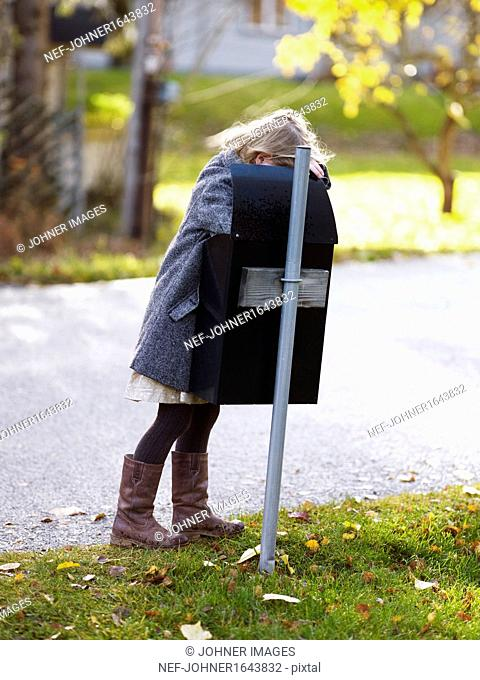 Girl looking for mail in mailbox