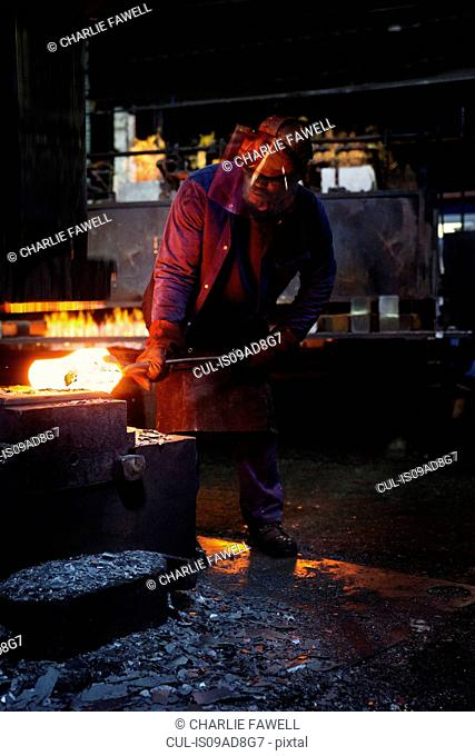Worker pre forms steel billet on 5 tonne clear space hammer before it will be presented to set of two dies to be fully forged in hammer