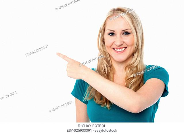 Young woman pointing at copy space area