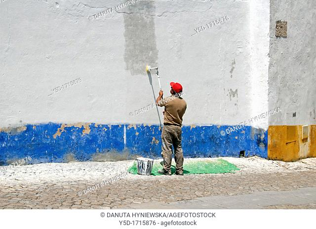 Man renewing paints on house wall with symbolic Portuguese colors white, blue, yellow, Obidos, Portugal