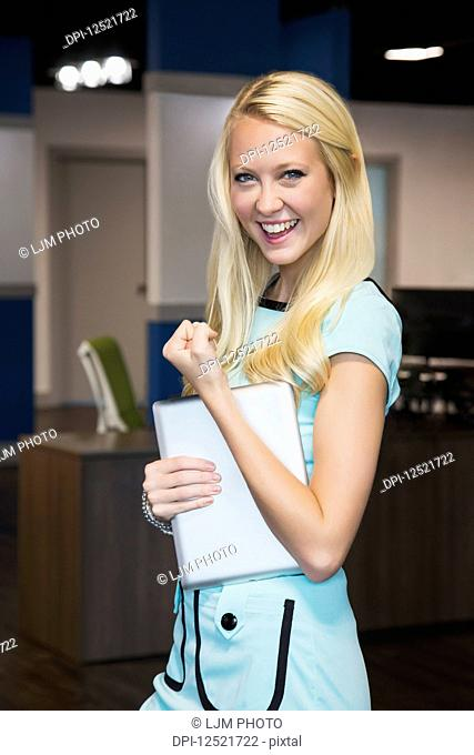 Beautiful young millennial business woman with long blond hair posing for the camera in the workplace, giving a sign of success; Edmonton, Alberta, Canada
