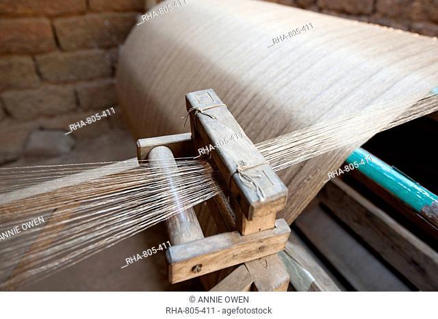 Silk thread being spun on large handmade wooden wheel, rural Orissa, India, Asia