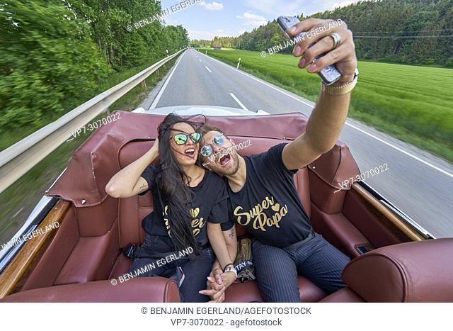 Couple taking selfie while driving in luxury oldtimer. Turkish ethnicity. High society. Bloggers Adem Bayalan and Emine Feruz Bayalan