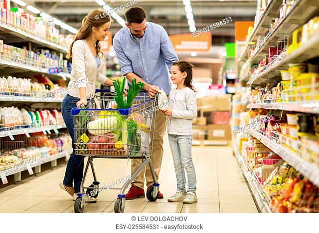 sale, consumerism and people concept - happy family with child and shopping cart buying food at grocery storeor supermarket