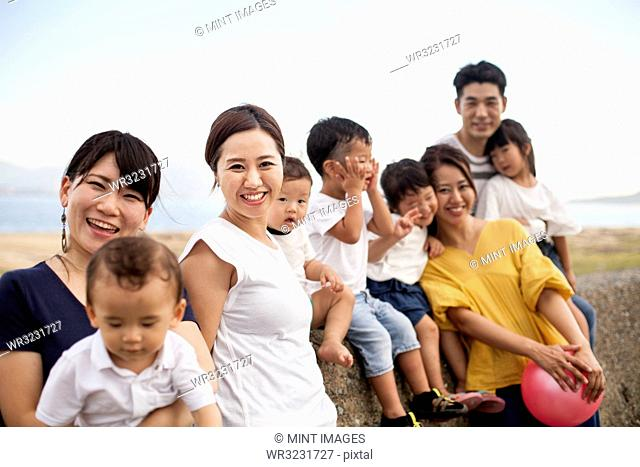 Group portrait of Japanese families with young children on promenade by ocean, smiling at camera
