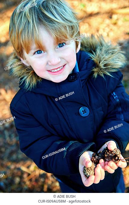 Young boy holding pine cones in hands