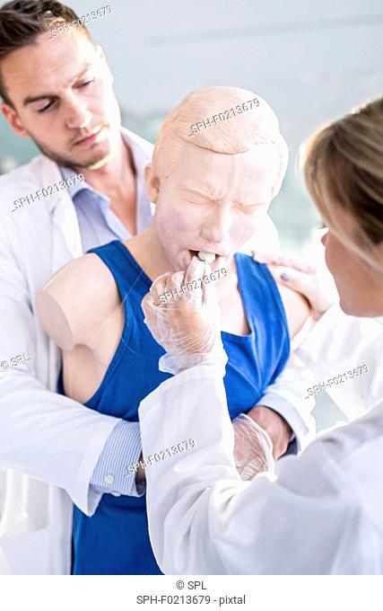 Doctor practising Heimlich manoeuvre