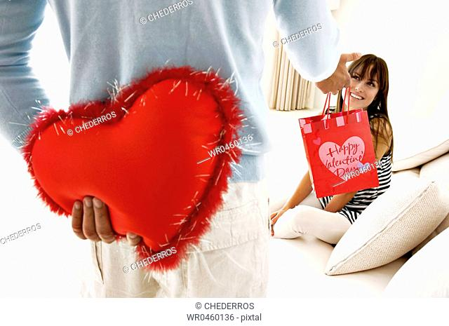 Mid section view of a man hiding a heart shaped cushion and giving a gift to a young woman