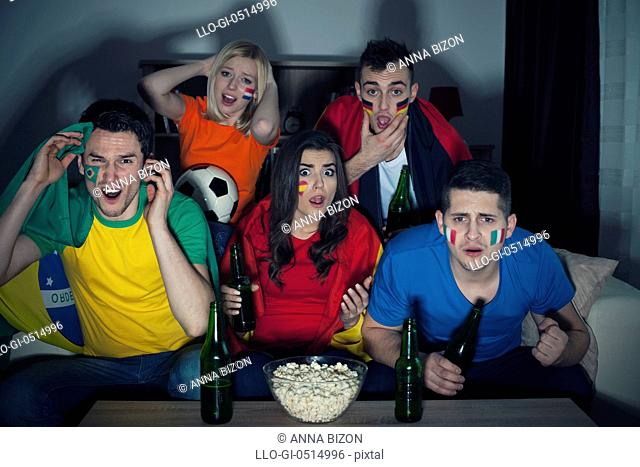 Shocked friends from different country watching soccer match on TV. Debica, Poland
