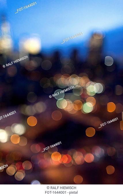 Defocused image of illuminated lights in city at dusk