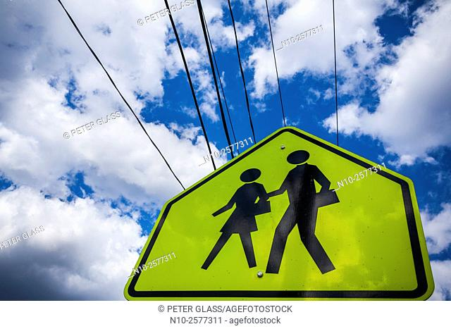 Children crossing sign against a cloudy sky