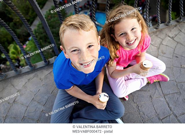 Portrait of brother and sister with ice cream cones sitting on balcony looking up to camera