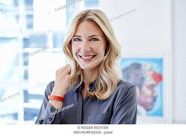 Portrait of smiling businesswoman wearing activity band