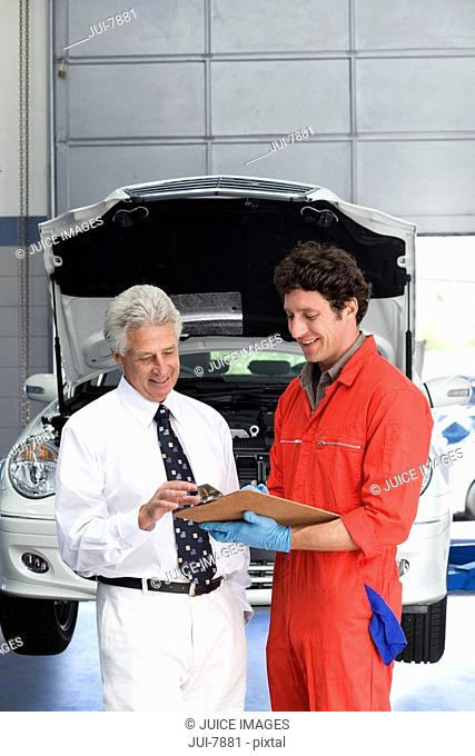 Car mechanic, in red overalls and protective gloves, talking to male customer beside car with open bonnet in auto repair shop, holding clipboard, smiling