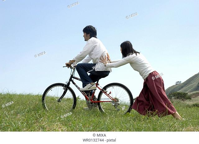Young woman pushing young man on bicycle