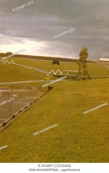 A landscape shot, consisting of manicured grass, a network of roads, a bridge, and a parking lot, Camp Eagle, Vietnam, 1964