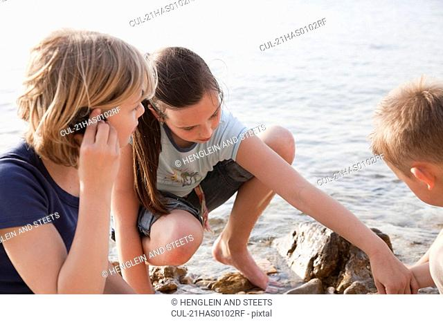 Children listening to shells at beach