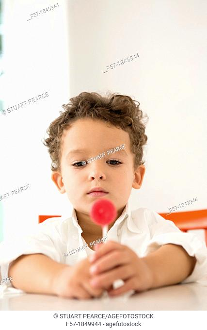 Four year old boy with a red lollipop