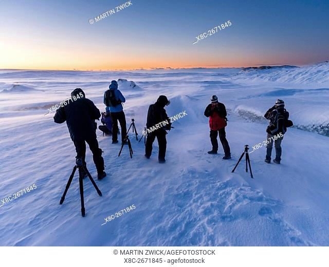 Photographers at sunrise and in a winter storm on the glacier Breithamerkurjoekull in the Vatnajoekull NP . europe, northern europe, iceland, February