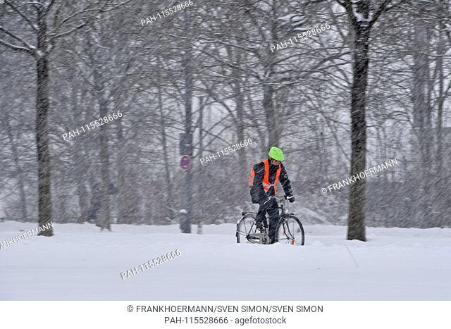 Snow chaos on the streets of Bavaria - probably the one who gets to his workplace by bike, like this cyclist with signal vest driving on a snow-covered