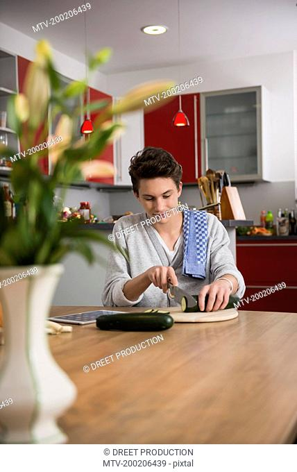 Young man preparing food in the kitchen, Munich, Bavaria, Germany