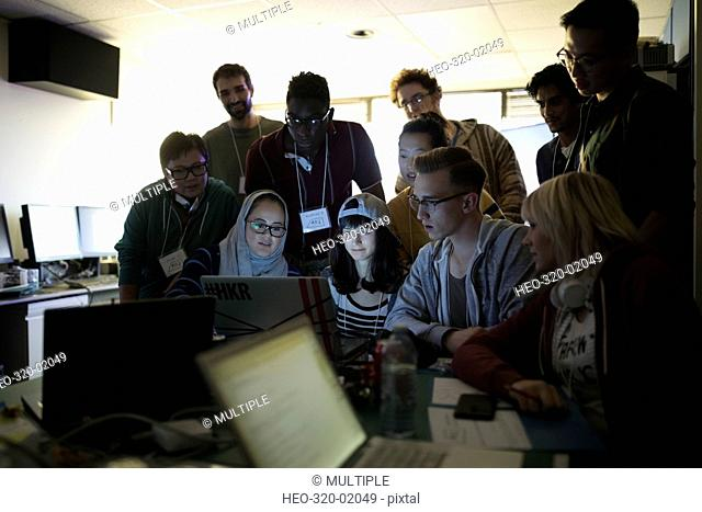 Young hacker team working hackathon at laptop in dark office