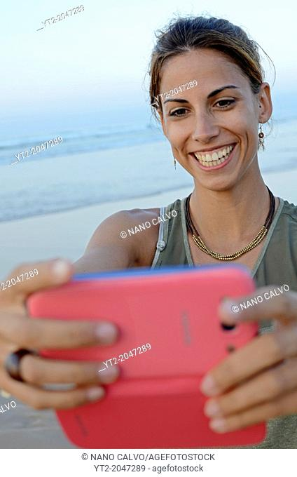 Attractive young woman takes a photo with her mobile phone